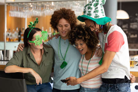 Diverse group of happy friends celebrating st patrick's day looking at smartphone at a bar. fun during celebration of the irish patron saint's day.