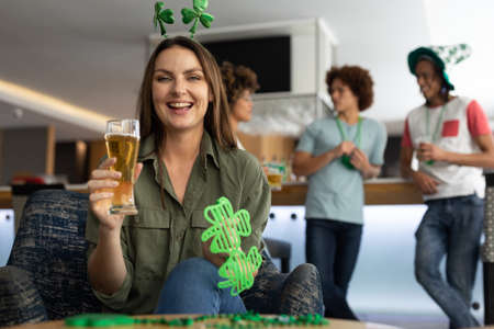 Portrait of caucasian woman wearing deely boppers and holding beer celebrating st patrick's at a bar. fun with friends during celebration of the irish patron saint's day. Standard-Bild