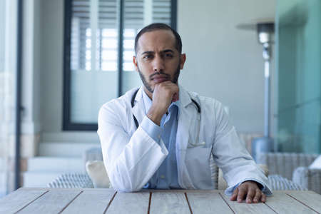 Portrait of caucasian male doctor looking at the camera and rubbing his chin. professional medical worker wearing stethoscope and lab coat.