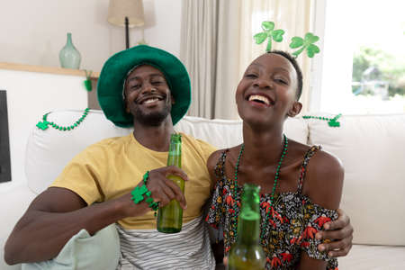 Portrait of laughing african american couple in st patrick's day costumes holding bottles of beer. staying at home in isolation during quarantine lockdown.
