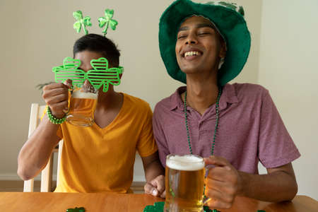Smiling mixed race gay male couple wearing st patrick's day costumes drinking beer. staying at home in isolation during quarantine lockdown.