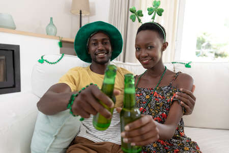 Portrait of smiling african american couple in st patrick's day costumes raising bottles of beer. staying at home in isolation during quarantine lockdown.