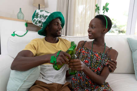 Smiling african american couple in st patrick's day costumes embarcing and raising bottles of beer. staying at home in isolation during quarantine lockdown.