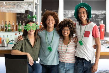 Portrait of diverse group of happy friends celebrating st patrick's day embracing at a bar. fun during celebration of the irish patron saint's day.