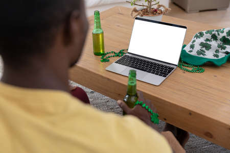 African american man holding bottle of beer making st patrick's day video call using laptop. staying at home in isolation during quarantine lockdown.