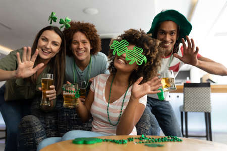 Portrait of diverse group of happy friends celebrating st patrick's day holding beers and waving. fun during celebration of the irish patron saint's day.
