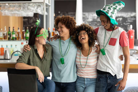 Diverse group of friends celebrating st patrick's day embracing and laughing at a bar. fun with friends during celebration of the irish patron saint's day. Standard-Bild