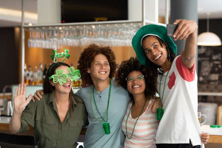Diverse group of happy friends celebrating st patrick's day taking selfie at bar. fun during celebration of the irish patron saint's day.
