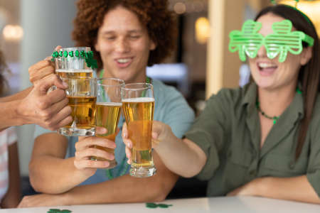 Diverse group of happy friends celebrating st patrick's day making toast with glasses of beer at bar. fun during celebration of the irish patron saint's day. Standard-Bild