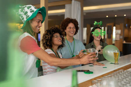 Diverse group of happy friends celebrating st patrick's day at a bar. fun during celebration of the irish patron saint's day. Standard-Bild