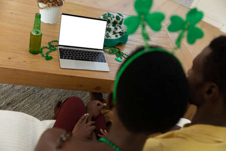 African american couple on st patrick's day video call using laptop with copy space on screen. staying at home in isolation during quarantine lockdown.