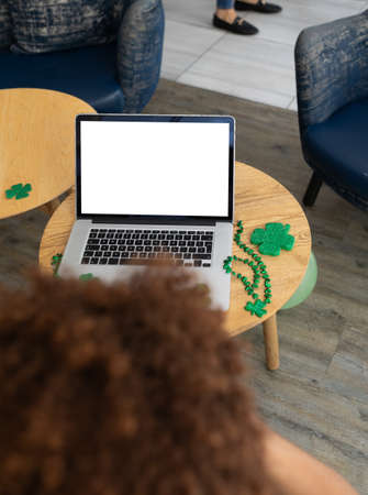 Mixed race woman celebrating st patrick's day on laptop video call with copy space on screen. fun during celebration of the irish patron saint's day. Standard-Bild