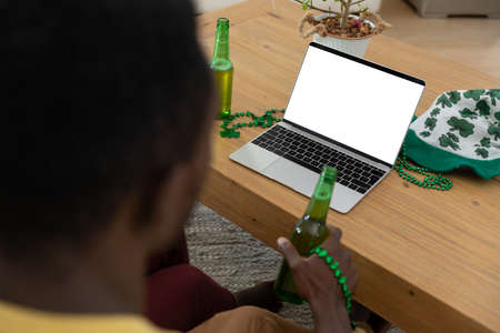 African american man with beer on st patrick's day video call using laptop with copy space on screen. staying at home in isolation during quarantine lockdown.