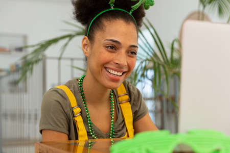 Happy mixed race woman celebrating st patrick's day making video call and smiling. staying at home in isolation during quarantine lockdown.