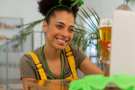 Happy mixed race woman celebrating st patrick's day making video call raising glass of beer. staying at home in isolation during quarantine lockdown.