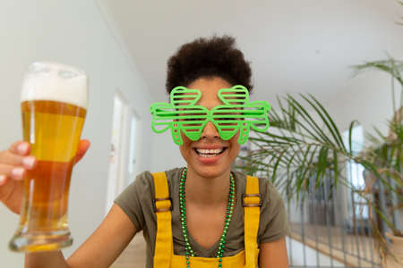 Mixed race woman celebrating st patrick's day making video call holding a beer. staying at home in isolation during quarantine lockdown.
