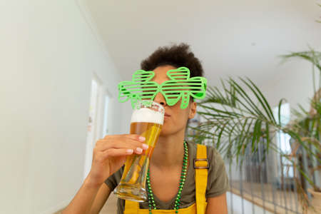Mixed race woman celebrating st patrick's day making video call drinking a beer. staying at home in isolation during quarantine lockdown.