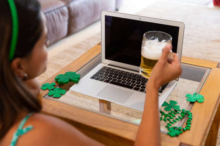 Caucasian woman celebrating st patrick's day making video call using laptop holding beer. staying at home in isolation during quarantine lockdown. Standard-Bild
