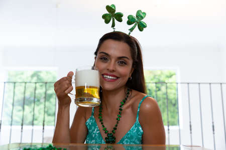 Caucasian woman celebrating st patrick's day making video call wearing deely boppers holding beer. staying at home in isolation during quarantine lockdown.