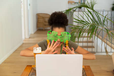 Happy mixed race woman celebrating st patrick's day making video call and waving. staying at home in isolation during quarantine lockdown. Standard-Bild