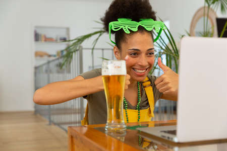 Happy mixed race woman with beer celebrating st patrick's day making video call giving thumbs up. staying at home in isolation during quarantine lockdown.