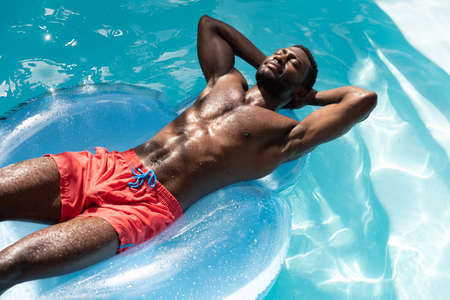African american man in swimming pool sunbathing on inflatable. staying at home in isolation during quarantine lockdown. Archivio Fotografico