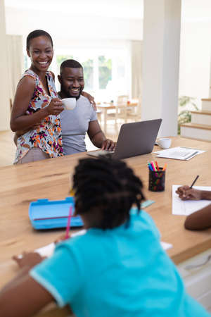 Happy african american parents using laptop embracing holding coffee with kids working at the table. staying at home in isolation during quarantine lockdown.