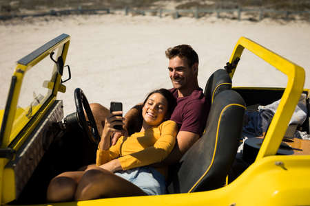 Happy caucasian couple sitting in beach buggy by the sea relaxing. beach break on summer holiday road trip. Foto de archivo