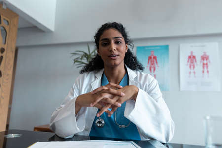 Mixed race female doctor at desk talking and gesturing during video call consultation. telemedicine, online healthcare services during quarantine lockdown