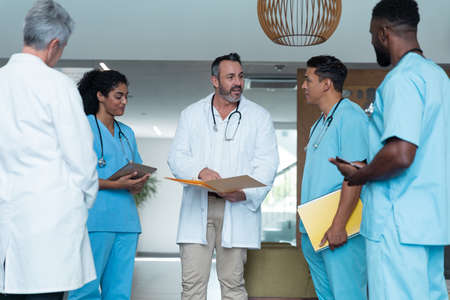 Diverse male and female doctors standing in hospital corridor and discussing. medicine, health and healthcare services. Stockfoto
