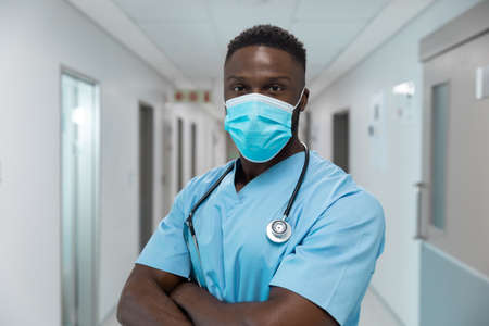 Portrait of african american male doctor wearing face mask standing in hospital corridor. medicine, health and healthcare services during coronavirus covid 19 pandemic.