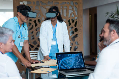 Diverse male and female doctors wearing face masks sitting at table and using vr glasses. medicine, health and healthcare services.