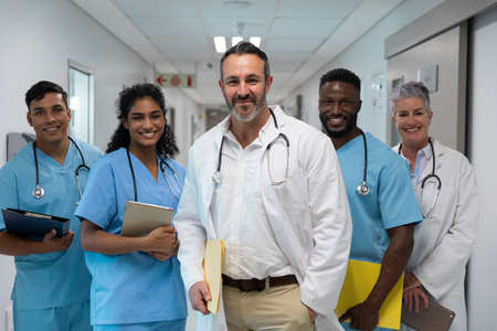 Portrait of diverse group of male and female doctors holding files, smiling in hospital corridor. medicine, health and healthcare services. Stockfoto