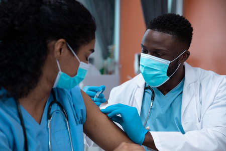 Mixed race couple of doctors wearing face masks making injection. medicine, health and healthcare services during coronavirus covid 19 pandemic. Stockfoto
