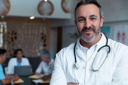 Portrait of smiling caucasian male doctor, with colleagues in discussion in the background. medicine, health and healthcare services.