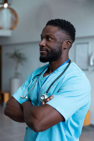 Portrait of african american male doctor with stethoscope wearing scrubs in hospital. medicine, health and healthcare services during covid 19 coronavirus pandemic. Stockfoto