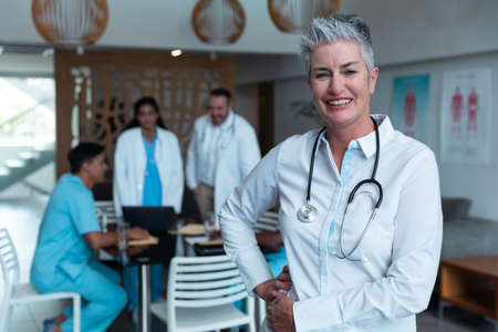 Portrait of smiling caucasian female senior doctor, with colleagues in discussion in the background. medicine, health and healthcare services.