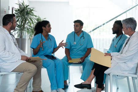 Diverse male and female doctors sitting in hospital corridor and discussing. medicine, health and healthcare services. Stockfoto