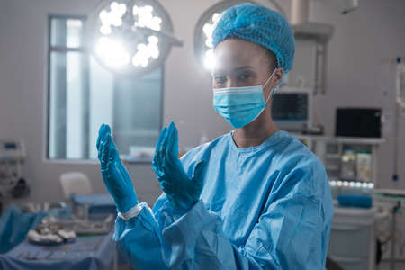 Mixed race female surgeon wearing face mask and protective clothing in operating theatre. medicine, health and healthcare services during covid 19 coronavirus pandemic.