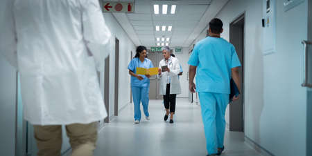 Diverse couple of female doctors walking through hospital corridor discussing. medicine, health and healthcare services.