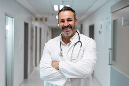 Portrait of mixed race male doctor smiling and standing in hospital corridor. medicine, health and healthcare services. Stockfoto