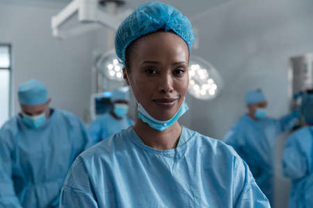 Smiling mixed race female surgeon with face mask and protective clothing in operating theatre. medicine, health and healthcare services during covid 19 coronavirus pandemic.