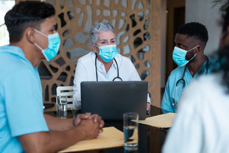 Caucasian female senior doctor and diverse hospital colleagues wearing face masks sitting at meeting. medicine, health and healthcare services during covid 19 coronavirus pandemic. .