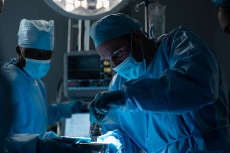 Caucasian male surgeon wearing face mask and protective clothing during operation in hospital. operating theatre. medicine, health and healthcare services during covid 19 coronavirus pandemic.