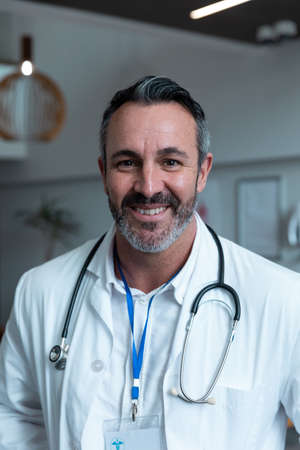 Portrait of smiling caucasian male doctor with stethoscope wearing lab coat in hospital. medicine, health and healthcare services during covid 19 coronavirus pandemic.