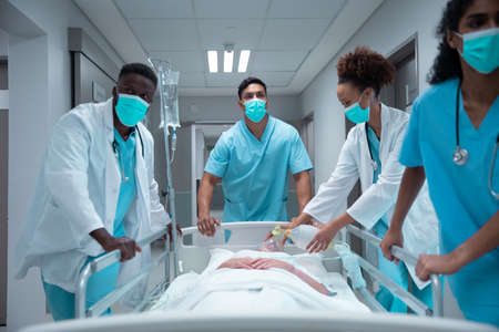 Mixed race doctors wearing face masks transporting patient in hospital bed. medicine, health and healthcare services during coronavirus covid 19 pandemic. Stockfoto