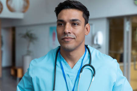 Portrait of mixed race male doctor with stethoscope wearing scrubs in hospital. medicine, health and healthcare services during covid 19 coronavirus pandemic.