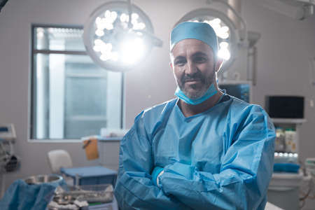 Smiling caucasian male surgeon with face mask wearing protective clothing in operating theatre. medicine, health and healthcare services during covid 19 coronavirus pandemic.