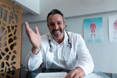 Mixed race male doctor at desk talking and gesturing during video call consultation. telemedicine, online healthcare services during quarantine lockdown