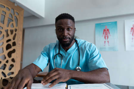 African american male doctor at desk talking and gesturing during video call consultation. telemedicine, online healthcare services during quarantine lockdown.
